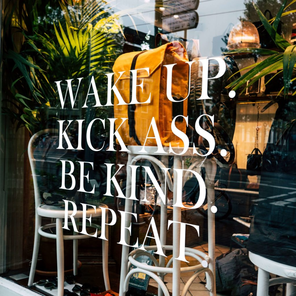 """Retail storefront with white window vinyl that says """"Wake up. Kick ass. Be kind. Repeat."""""""